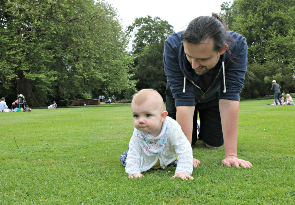 Eleanor and daddy crawling on the lawn at Mottisfont