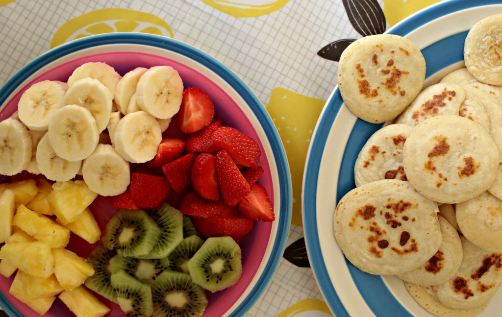 Drop scones with a selection of fruit - banana, strawberries, kiwi and pineapple
